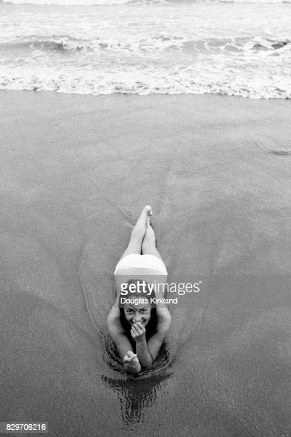 French actress Jeanne Moreau laying on the wet sand at a beach in Cuernavaca Mexico 1965
