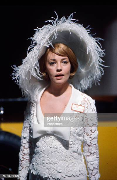 French actress Jeanne Moreau pictured wearing a large white feather lined hat in a scene from the film 'The Yellow Rolls-Royce' in 1964.