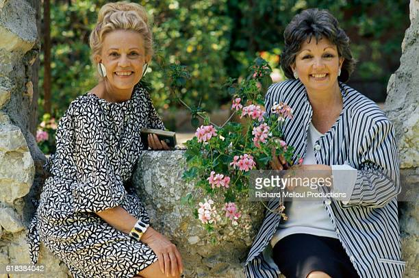 French actress Jeanne Moreau sits next to some flowers with her sister Michele The two sisters were in Cannes to attend the 40th Cannes Film Festival