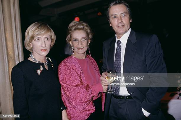 French actress Jeanne Moreau surrounded by writer Françoise Sagan and actor Alain Delon after the premiere of the play Le Récit de la servante...