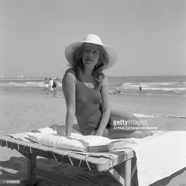 French actress Jeanne Moreau, wearing a swimming suit and a wide-brimmed hat, sitting on a sunbed, a book next to her, the seashore and some people...