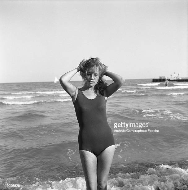French actress Jeanne Moreau wearing a swimming suit holding her hair standing on the seashore feet in the water Lido Venice 1961