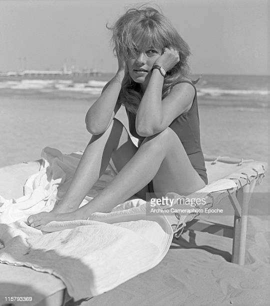 French actress Jeanne Moreau wearing a swimming suit sitting on a sunlounger with her elbows on the knees at Lido beach Venice 1961