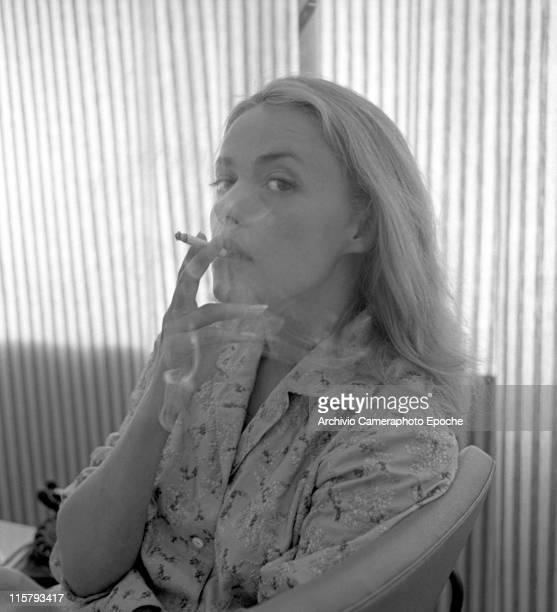 French actress Jeanne Moreau wearing an embroidered shirt portrayed while smoking a cigarette and making smoke spirals a striped curtain in the...