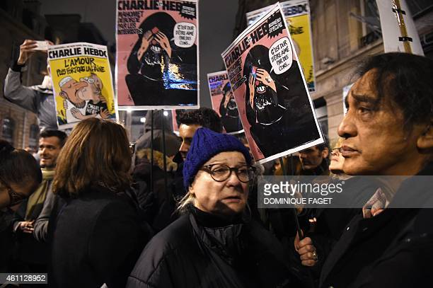 French actress Josiane Balasko holds a Charlie Hebdo's front page as she takes part in a gathering at the Place de la Republique in Paris on January...