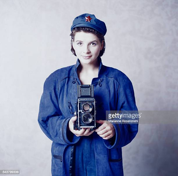 French actress Juliette Binoche wears a Mao coat and hat while holding a duallens reflex camera as if to take a picture