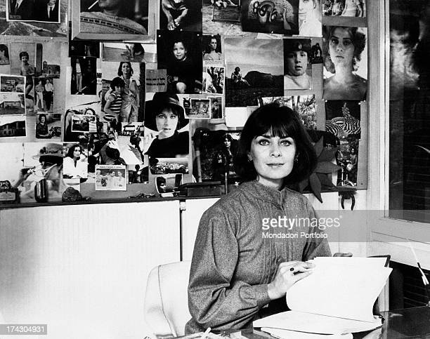 French actress Juliette Mayniel leafing through a book Behind her a wall covered with pictures Rome 1970s