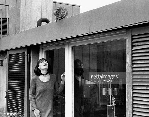 French actress Juliette Mayniel watching a cat from the door of a conservatory Rome 1970s