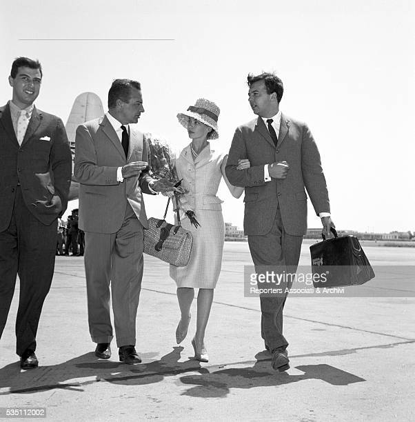 French actress Leslie Caron arm in arm with her husband and British actor Peter Hall and Italian actor Rossano Brazzi welcoming them at Ciampino...