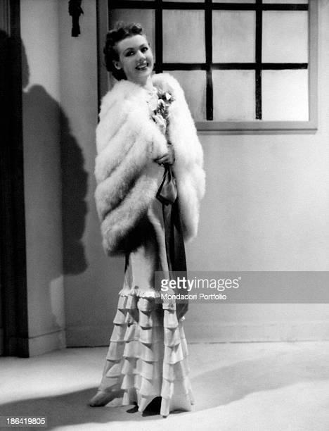 French actress Liliane Lesaffre on the set of the movie Café de Paris wearing an elegant long robe and a white fur stole France 1938