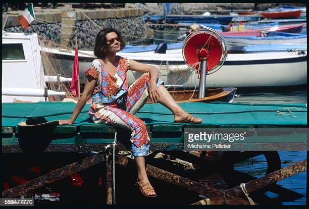 French actress Macha Meril enjoys the sunshine on the docks of an Italian port.
