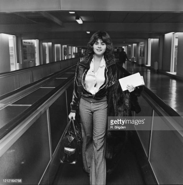 French actress Maria Schneider carrying documents in one hand a holdall in the other a fur coat over her arm as she walks through Heathrow Airport in...
