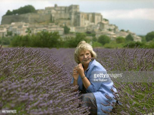 French actress MarieChristine Barrault stops to smell the flowers in a field of lavender next to the village of Grignan in the Drome region of France...