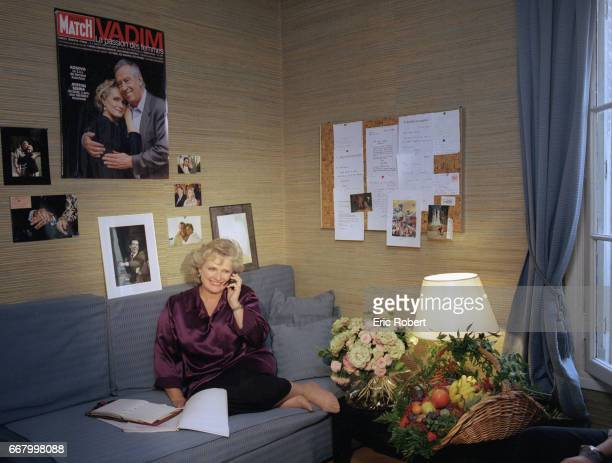French actress MarieChristine Barrault talks on the phone in her apartment Photographs and publicity of her husband director Roger Vadim cover the...