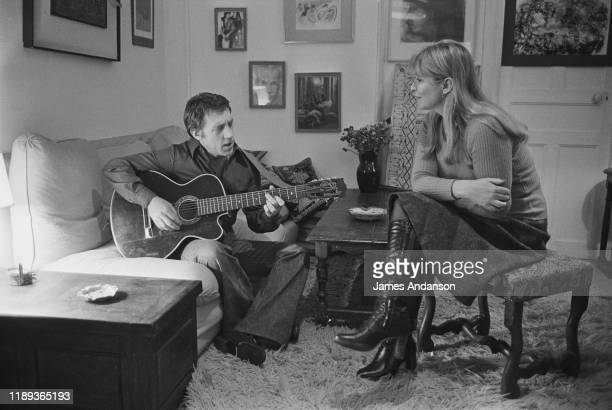 French actress Marina Vlady is serenaded by her husband Vladimir Vysotsky a Russian antiestablishment actor poet songwriter and singer at their home...