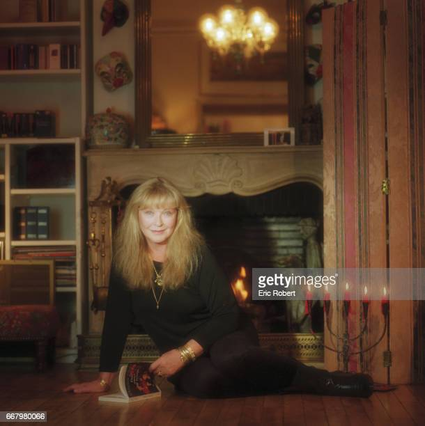French actress Marina Vlady reads a book in front of the fireplace in her living room