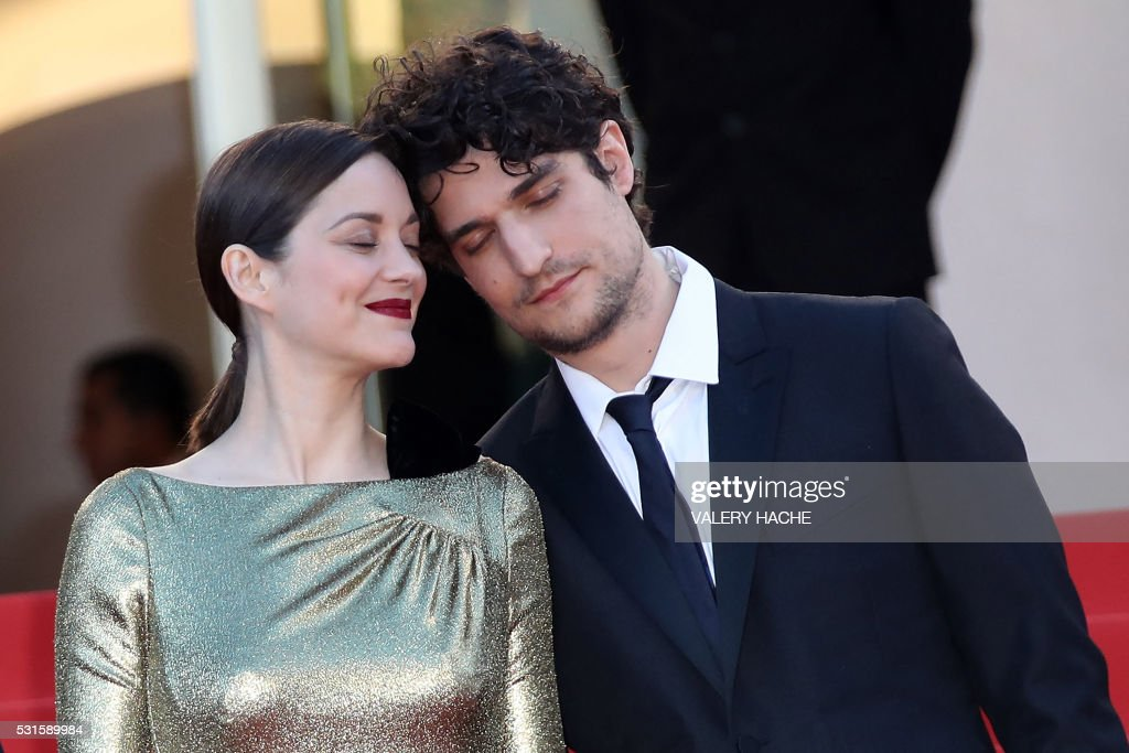 TOPSHOT - French actress Marion Cotillard (L) and French actor Louis Garrel pose as they arrive on May 15, 2016 for the screening of the film 'Mal de Pierres (From the Land of the Moon)' at the 69th Cannes Film Festival in Cannes, southern France. / AFP PHOTO / Valery HACHE