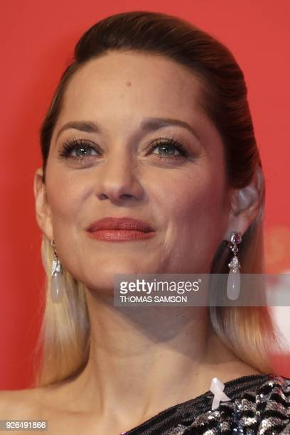 French actress Marion Cotillard wears a white ribbon in protest of violence against women as she poses during a photocall at the 43rd edition of the...