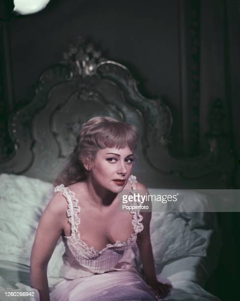 French actress Martine Carol posed seated on a bed wearing a nightdress during shooting of the film 'Nana' in Paris France in November 1954