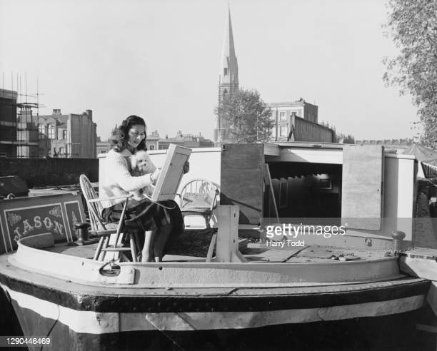 French actress Michele Clement sits painting with her pet poodle, Penny, on the deck of the Canaletto Gallery, in a converted canal boat on the Grand...