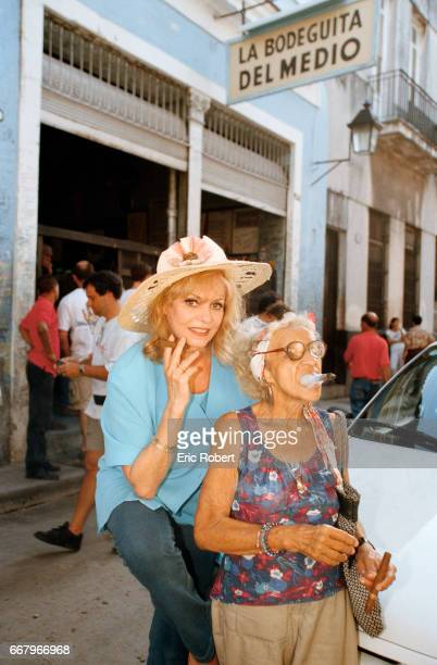 French actress Michele Mercier and an elderly woman smoke Cuban cigars on a busy Havana street Mercier was best known for her starring roles in the...