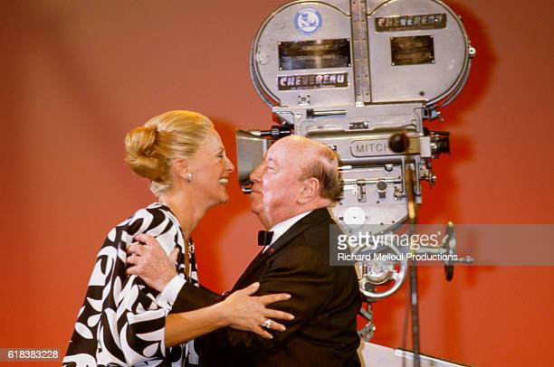 French actress Michele Morgan embraces French director Marcel Carne near a vintage movie camera at the Cannes Film Festival.