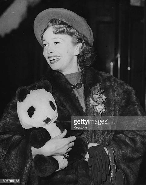 French actress Mila Parely smiles as she holds a toy panda bear arriving in London May 15th 1949