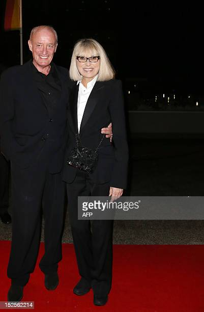 French actress Mireille Darc poses with an unidentified person as she arrives to attend the inauguration ceremony of the Cite du cinema a film...