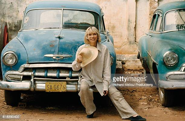 French actress Mireille Darc seated on the fender of an old Chevrolet on the set of the 1996 mini series Terre Indigo