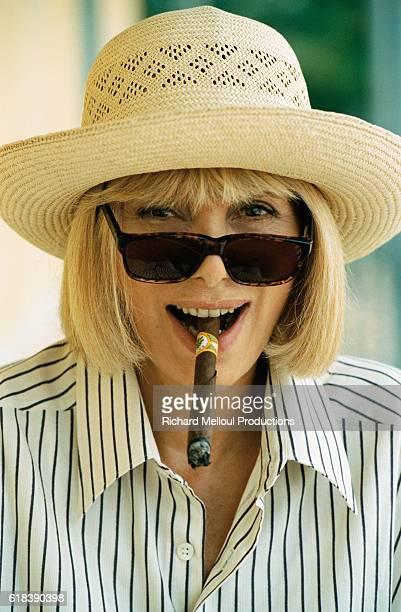 French actress Mireille Darc smokes a cigar on the set of the 1996 mini series Terre Indigo