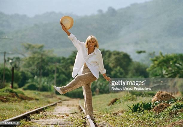 French actress Mireille Darc walks along railroad tracks on the set of the 1996 mini series Terre Indigo