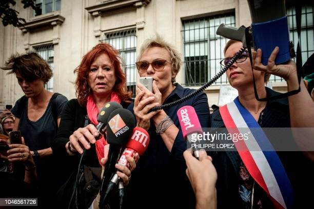 French actress Muriel Robin speaks with a megaphone past her partner Anne Le Nen French actress Eva Darlan and parliament member of leftwing party La...