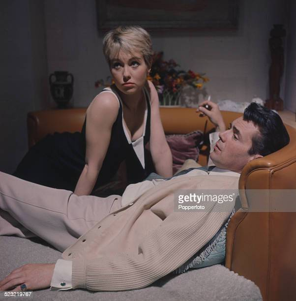 French actress Mylene Demongeot and English actor Dirk Bogarde pictured together on a large circula sofa on the set of the film Doctor in Distress in...
