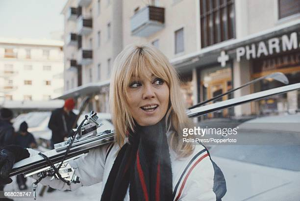 French actress Mylene Demongeot pictured carrying a pair of skis during a holiday at a ski resort in Switzerland in January 1971