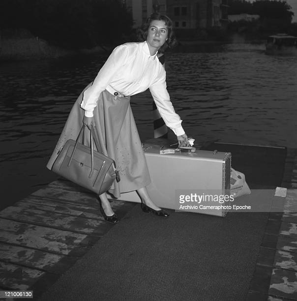 French actress Myriam Bru wearing a shirt and a skirt holding a handbag portrayed while lifting his luggage on a wharf Lido Venice 1958