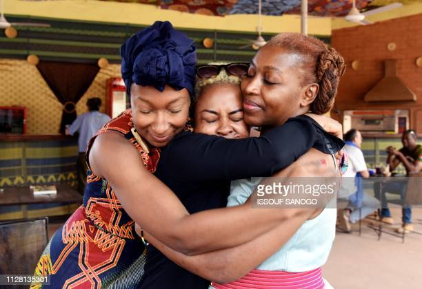 French actress Nadege Beausson Diagne, Burkina Faso's actress Azata Soro and Cameroon's activist and filmmaker Pascale Obolo hug on Febuary 28 during...