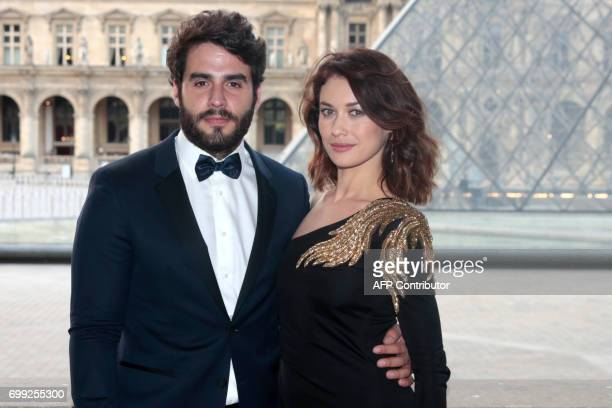 French actress Olga Kurylenko and her partner British actor Ben Cura pose as they arrive to attend a charity dinner organised by the American Friends...