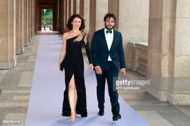 French actress Olga Kurylenko and her partner British actor Ben Cura arrive to attend a charity dinner organised by the American Friends of the...