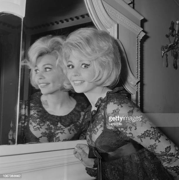 French actress Patricia Viterbo wearing a lace transparent dress poses next to a mirror UK 27th January 1965