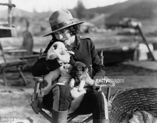 French actress Renee Adoree formerly Jeanne De La Fonte wearing a Mountie's uniform and cuddling a litter of puppies which were born on the set of...