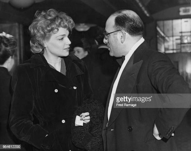 French actress Simone Signoret talks to producer Michael Balcon at the premiere of the film 'The Life and Adventures of Nicholas Nickleby' at the...