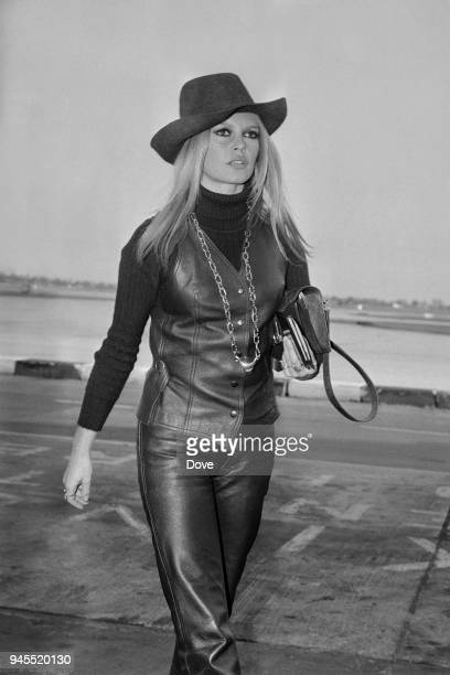 French actress, singer and fashion model Brigitte Bardot wearing leather waistcoat, high-collar shirt, leather pants and cowboy hat, Heathrow...