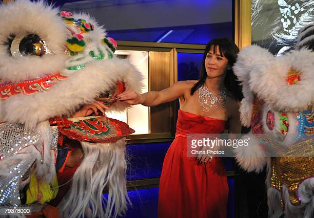 French actress Sophie Marceau hands out the Red Bag symbolizing good luck to a performer of a Lion Dance during a promotion of French jewellery brand...