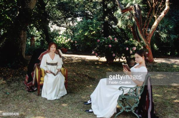 French actresses Isabelle Huppert and Marie Gillain sit and read books in a garden with trees in the background in a scene taken from the movie Le...