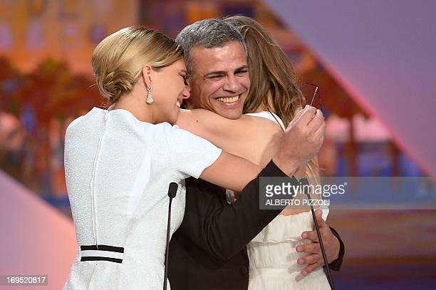 French actresses Lea Seydoux and Adele Exarchopoulos embrace FrenchTunisian director Abdellatif Kechiche after he was awarded on May 26 2013 with the...