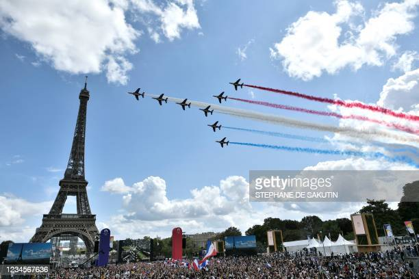 French aerial patrol 'Patrouille de France' fly over the fan village of The Trocadero set in front of The Eiffel Tower, in Paris on August 8, 2021...