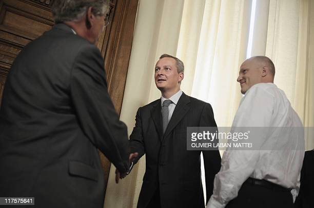 French Agriculture minister Bruno Le Maire shakes hands with a representative of a French milk producer trade-union prior to a meeting to discuss the...