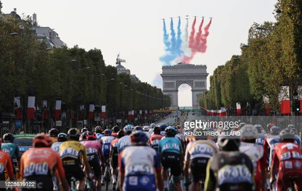 """French air force's aerobatics demonstration unit """"Patrouille de France"""" performs as the pack rides on the Champs Elysees avenue with the Arc de..."""