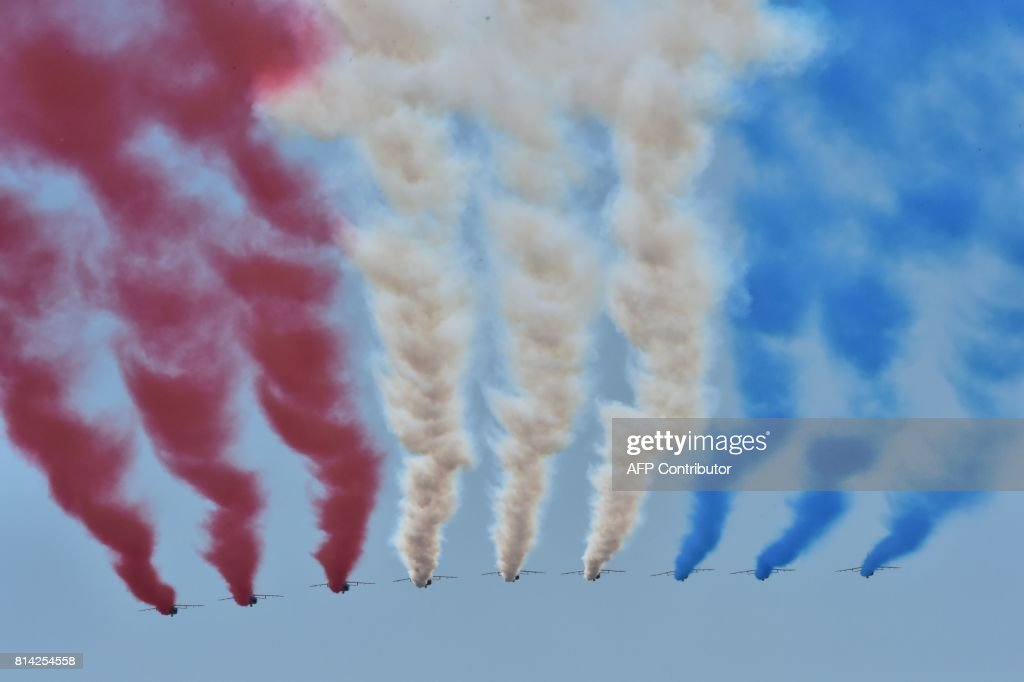 TOPSHOT - French AlphaJet of the Patrouille de France fly over Paris during the annual Bastille Day military parade on the Champs-Elysees avenue in Paris on July 14, 2017. Bastille Day, the French National Day, is held annually each July 14, to commemorate the storming of the Bastille fortress in 1789. This years parade on Paris's Champs-Elysees will commemorate the centenary of the US entering WWI and will feature horses, helicopters, planes and troops. /