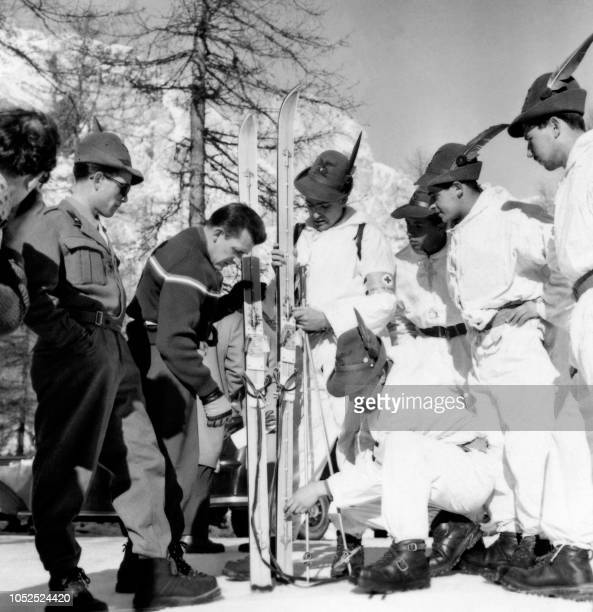 French alpine skier James Couttet shows his new skis to italian alpine warfare on January 27 1956 during the Winter Olympic Games in Cortina d'Ampezzo